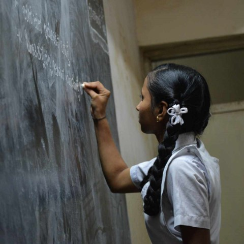 Picture of a child writing on a backboard with chalk