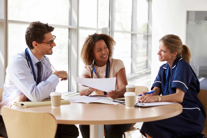 Picture of healthcare professionals discussing medical reports sitting at a table